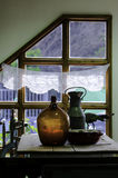 Alte hölzerne TabellenflaschenMilchflasche- und Emailkasserollen auf dem Hintergrund von Fenster stockfotos