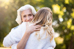 Alte hübsche Frau, die ihre Tochter umfasst Stockbild