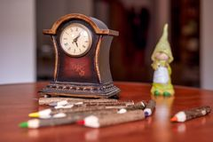 Alte h?lzerne Uhr und farbige Bleistifte lizenzfreies stockbild