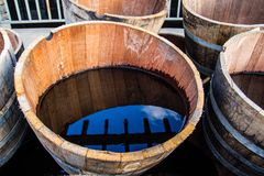 Alte halbe Fässer füllten mit Wasser, welches die Umgebungen reflektiert Stockbild