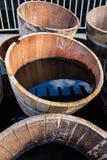 Alte halbe Fässer füllten mit Wasser, welches die Umgebungen reflektiert Lizenzfreies Stockfoto