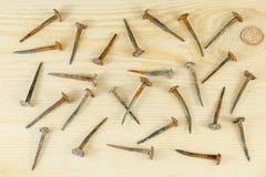 Alte hand-geschmiedete Nägel, die chaotisch auf einem Brett liegen stockfotos