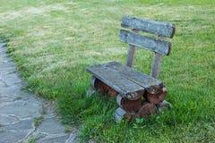 Alte handgemachte Holzbank, die auf Rasen vom Recht von San steht Stockbilder