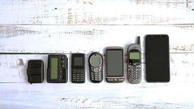 Alte Handys und Pagers lokalisiert auf weißem hölzernem Hintergrund stockbilder