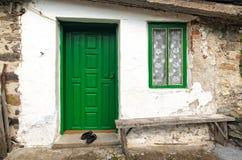 Alte Hausmauer mit Holztür, Fenster und Bank Lizenzfreies Stockbild