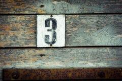 Alte Hausnummerplatte 3 auf altem grungy Grün malte Tür Stockfoto