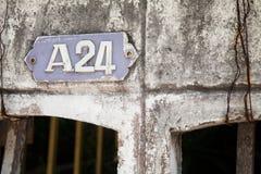 Alte Hausnummerplatte A 24 auf einer sehr schäbigen alten Wand Zahlplakette Lizenzfreies Stockbild