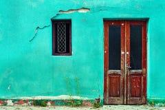 Alte Hauswand mit hölzerner Tür und Fenster Stockfotografie