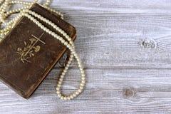 Alte heilige Bibel und Rosenkranzperlen auf rustikalem Holztisch lizenzfreies stockbild