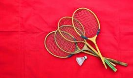 Alte hölzerne Federballschläger und Federball auf rotem Hintergrund Stockfoto