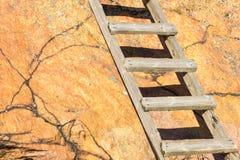 Alte hölzerne Leiter, die oben ein roter Felsen geht Stockfoto