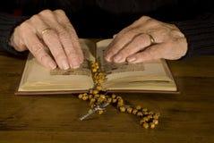 Alte Hände durch das Lesen der Bibel Lizenzfreies Stockfoto
