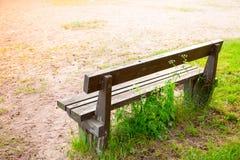 Alte Holzbank auf Gras im Sommerpark Lizenzfreies Stockbild