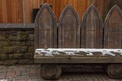 Alte Holzbank bedeckt in Schneetraditionellem geschnitzt graviert stockbild