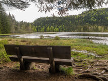 Alte Holzbank durch See in den Hügeln Lizenzfreie Stockbilder