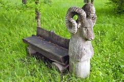Alte Holzbank im Park mit RAM-Skulptur Stockfotos