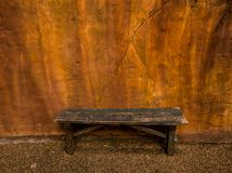 Alte Holzbank mit orange Betonmauerfoto stockfoto