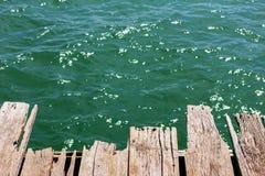 Alte Holzbrücke auf dem Meerwasser, dem Meer und dem Ozean Lizenzfreies Stockfoto