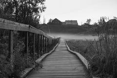Alte Holzbrücke zum Dorfhügel Weinlesegotisches rustikales Schwarzweiss-Foto Lizenzfreies Stockbild
