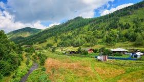 Alte Holzhäuser mit Gärten im Tal eines kleinen Stromes Stockfotos