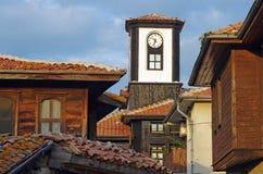 Alte Holzhäuser mit Glockenturm Stockbild