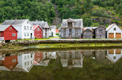 Alte Holzhäuser mit Reflexion in dem Teich, Fuß des Berges in Laerdal, Norwegen Stockfotografie