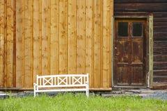Alte Holzhausfassade mit Bank und Grünpflanzen Lizenzfreies Stockfoto