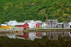 Alte Holzhäuser mit Reflexion in dem Teich, Fuß des Berges in Laerdal, Norwegen Stockfoto
