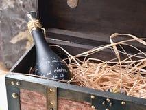 Alte Holzkiste öffnete sich mit einer deco Flasche im dunklen Glas auf Raffiabast stockfotos