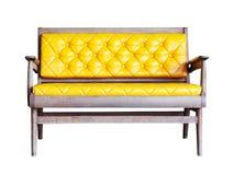 Alte Holzstühle der Weinlese mit dem gelben Kissen lokalisiert Stockfoto
