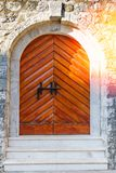 Alte Holztür auf Schmutz-Backsteinmauer Sun-Licht auf antiker Tür Lizenzfreie Stockfotografie
