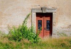Alte Holztür in der alten Wand Lizenzfreie Stockfotografie