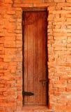 Alte Holztür in der Backsteinmauer Lizenzfreie Stockfotografie