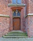 Alte Holztür in der Backsteinmauer mit Eiseninstallationen, Schritten und dekorativen Fenstern Lizenzfreie Stockbilder