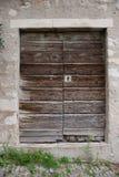 Alte Holztür in der Steinwand Stockbild