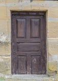 Alte Holztür in einer Steinwand Stockfoto