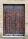 Alte Holztür in einer Steinwand Stockfotografie