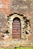 Alte Holztür in gealterter Backsteinmauer Stockfotografie