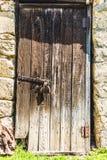 Alte Holztür im Dorf mit einem großen rostigen Verschluss Lizenzfreies Stockfoto