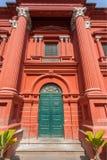 Alte Holztür im enormen roten historischen Gebäude Stockfotografie