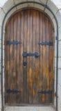 Alte Holztür innerhalb der alten Steinwand Lizenzfreies Stockbild