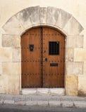 Alte Holztür mit Bogen in der Steinwand Stockfoto