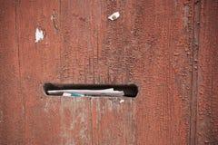 Alte Holztür mit dem Briefkasten an Stockbilder