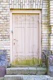 Alte Holztür mit dem Zerreiben in einer Backsteinmauer Stockfotografie