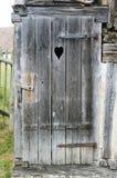 Alte Holztür mit einem geschnitzten Herzen Lizenzfreies Stockfoto