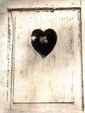Alte Holztür mit einem geschnitzten romantischen Herzen Stockfotografie