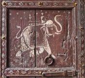 Alte Holztür mit einer Abbildung eines Elefanten. Fragment. Lizenzfreie Stockfotos