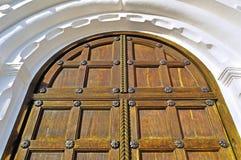 Alte Holztür mit Metallnieten und Bogen des weißen Steins Lizenzfreie Stockbilder