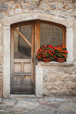 Alte Holztür mit roten Blumen Lizenzfreies Stockbild