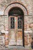 Alte Holztür mit Ziegelsteintorbogen Lizenzfreies Stockbild